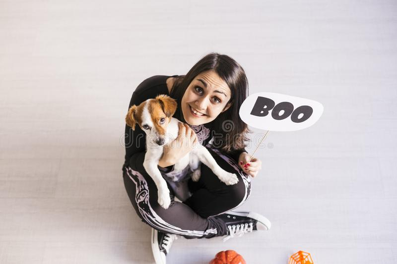 Top view of a young woman with her cute small dog wearing getting ready for Halloween. Woman wearing a skeleton costume. Halloween. Concept. Indoors stock photos