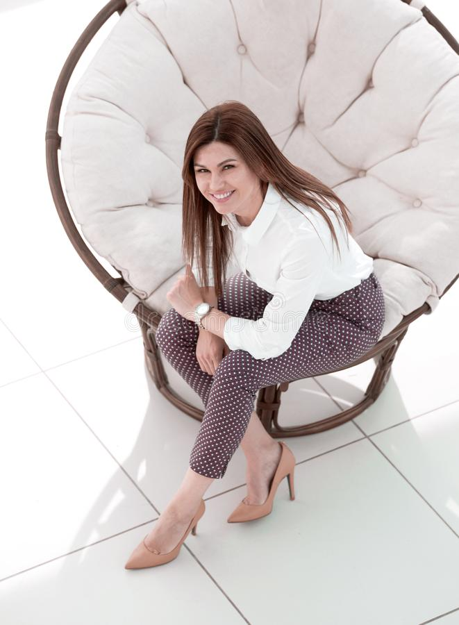 Top view.young woman sitting in soft round chair stock image