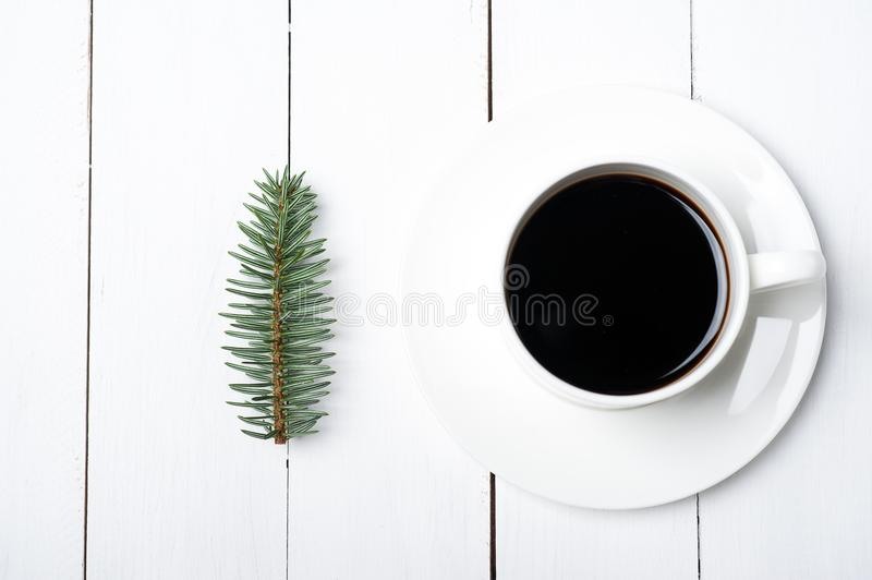 Top viewof winter composition of cup of coffee and fir tree branch on white wood background. Christmas morning in Scandinavian stock image