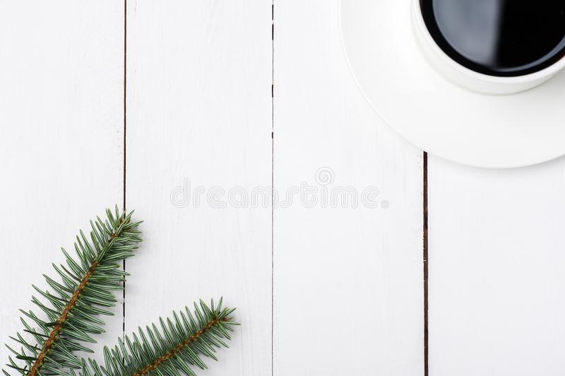 Top viewof winter composition of cup of coffee and fir tree branch on white wood background. Christmas morning in Scandinavian royalty free stock photography