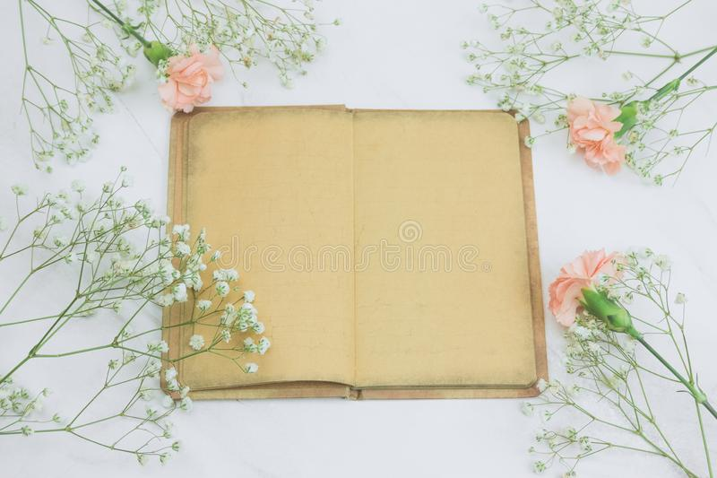 Vintage book with empty sheets and flowers on a marble background. Top view vintage book with empty sheets and flowers on a marble background royalty free stock images
