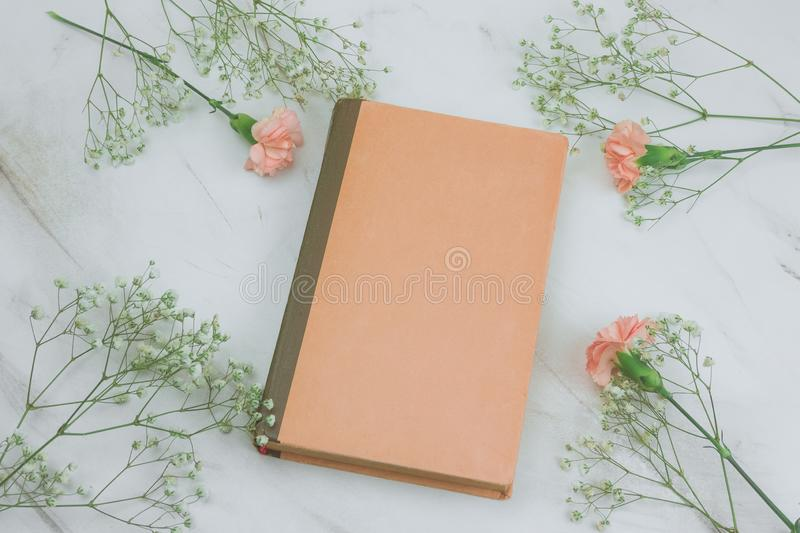 Vintage book with empty sheets and flowers on a marble background. Top view vintage book with empty sheets and flowers on a marble background stock image