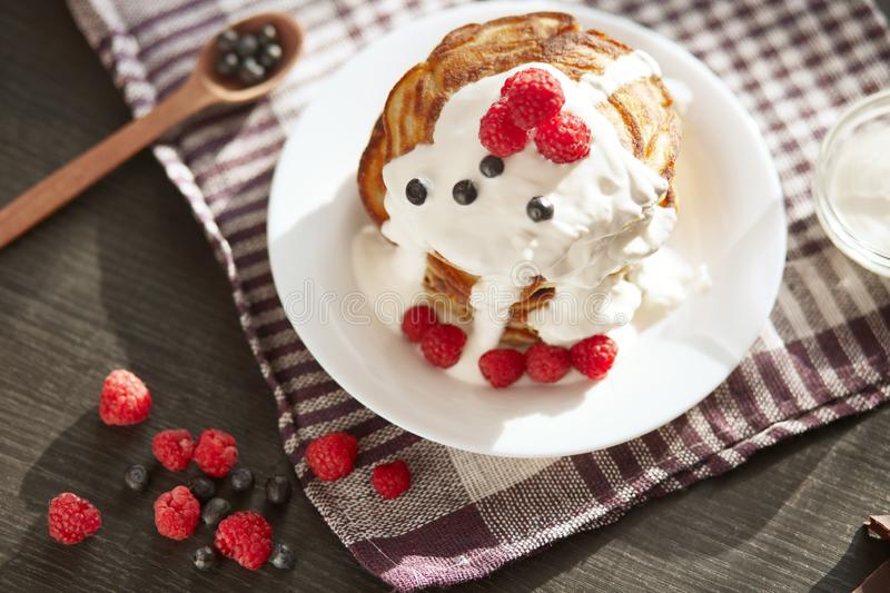 Top wiev of tasty pancakes on checkered cotton towel, muffins with sour cream, fresh blueberries and raspberries on white plate,. Spoon full of berries royalty free stock image