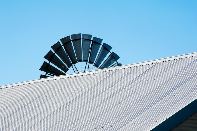 Top of a windmill over the corrugated roof of a shearing shed royalty free stock photography