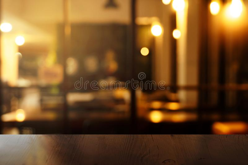 Top of wood table with blur orange light at bar or pub in the dark night background. Top of brown wood table with blur orange light at bar or pub in the dark royalty free stock photo