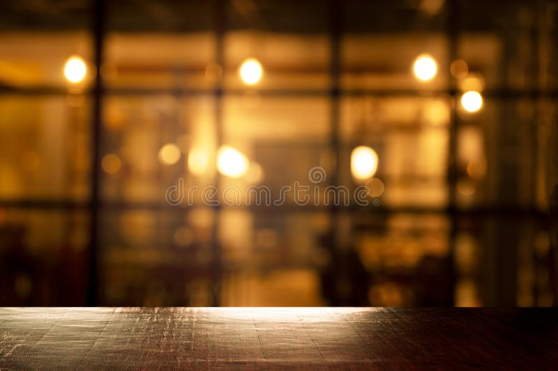 Top of wood table with blur orange light of pub in bar in the dark night background. Top of wood table with blur orange party light of pub in bar in the dark stock image