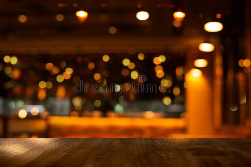 Top of wood table with bokeh of glor blur lamp light in party bar or pub in the Christmas night background. Top of wood table with bokeh of glor blur lamp light stock photo