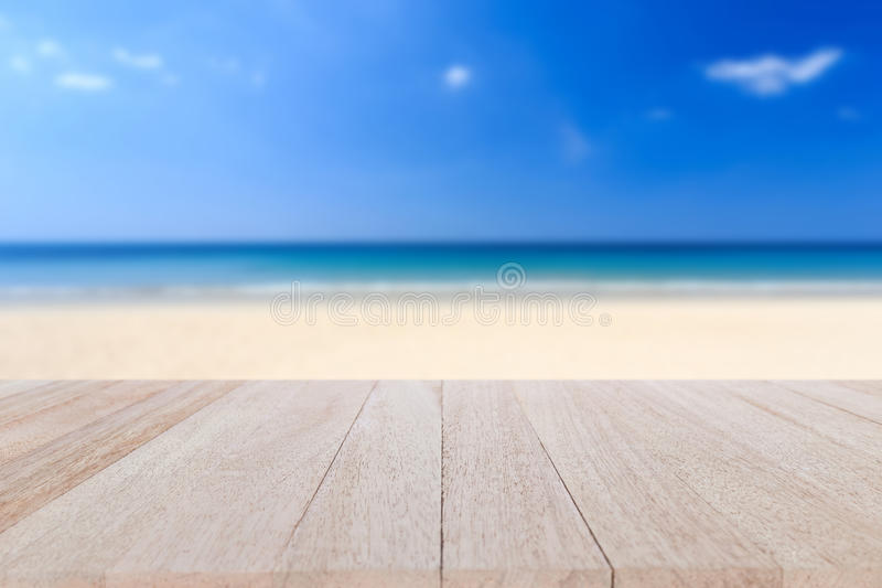 Top wooden table and blur of tropical beach background. Close up top wooden table and blur of tropical beach background stock photo