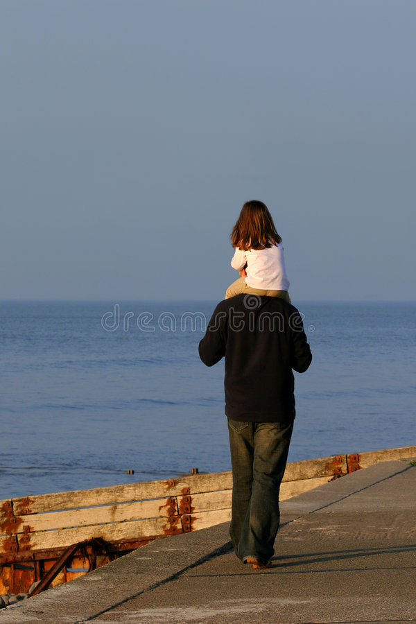 On Top Of The World. A man carrying a little girl on his shoulders and walking along a promenade next to the sea stock images