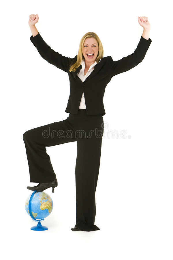 On Top Of The World. A beautiful blond businesswoman stands with her foot on a globe and raising her arms in conquering celebration royalty free stock images