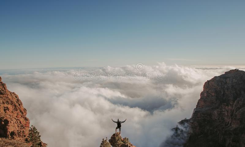 On the top of the world. Man on top of the mountain above the clouds royalty free stock image