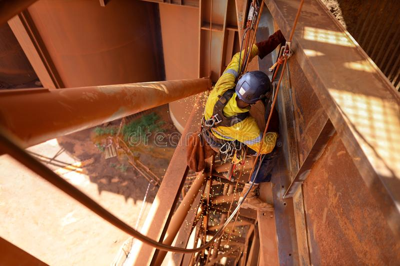 Tope view abseiler rope access repairer hanging in fall restraint position performing oxy acetylene cutting metal beam royalty free stock photo