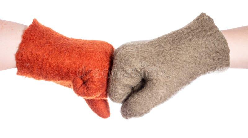 Topetón del puño de dos manos en guantes anaranjados y verdes fotos de archivo