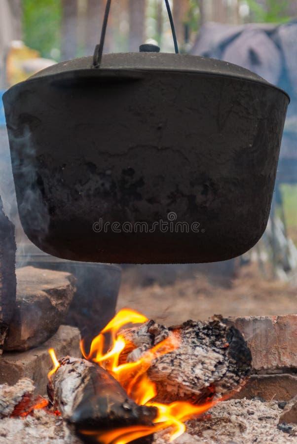 Topf, der im Wald über dem Feuer in der Kampagne hängt lizenzfreies stockfoto