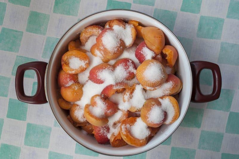 Topf mit den Aprikosen und Zucker bereit gekocht zu werden, um Stau zu machen stockfotografie