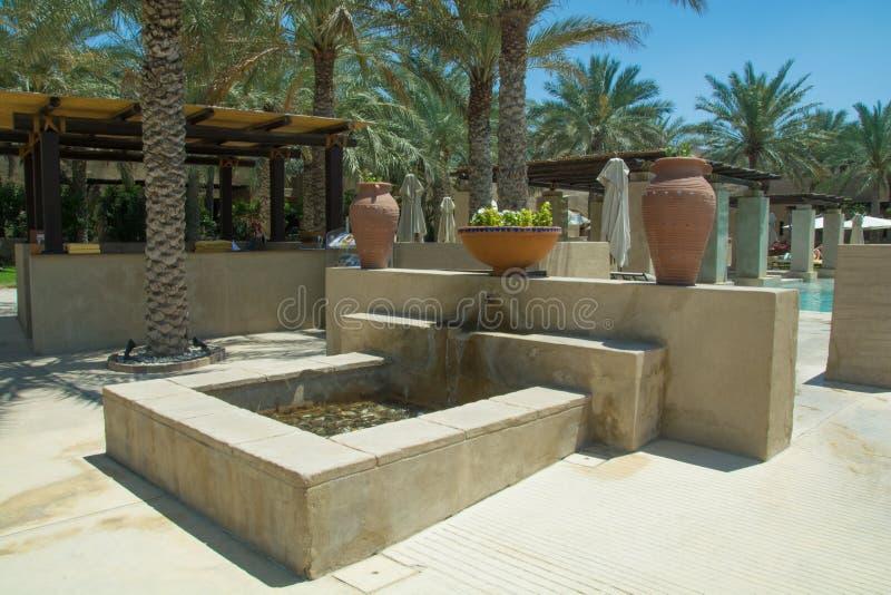 Topf und Krüge mit Blumen nahe Brunnen im schönen erstaunlichen Luxuserholungsort stockfoto