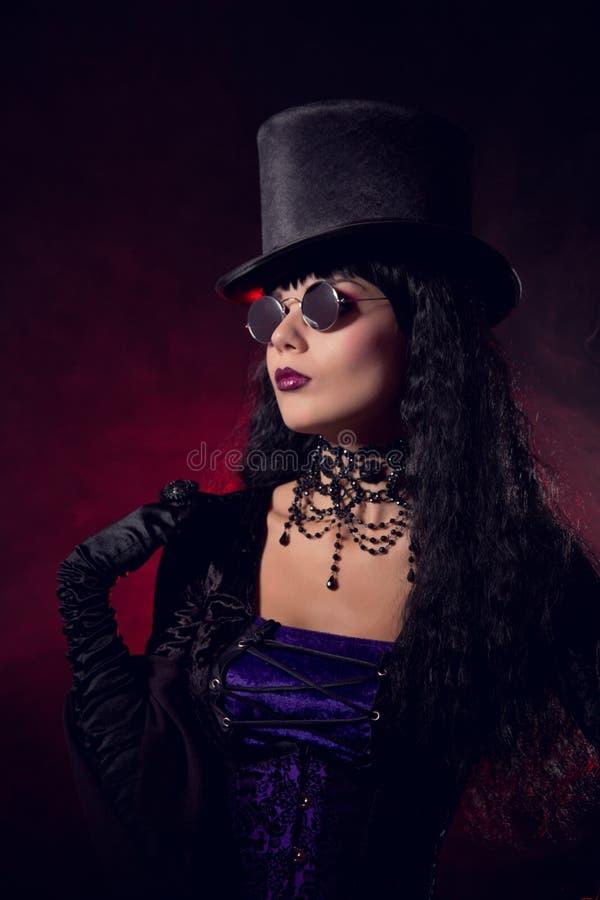 tophat和圆的镜片的吸血鬼哥特式女孩 库存照片