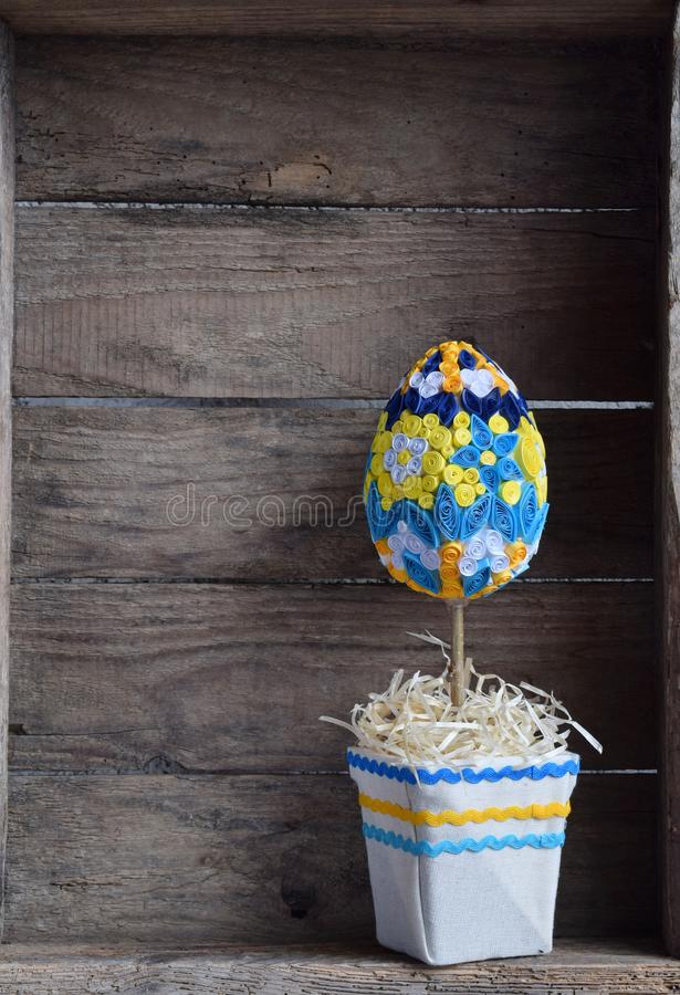 Topiary egg made in quilling technique on wooden background. Easter decorations or handmade gift. Copy space royalty free stock photo