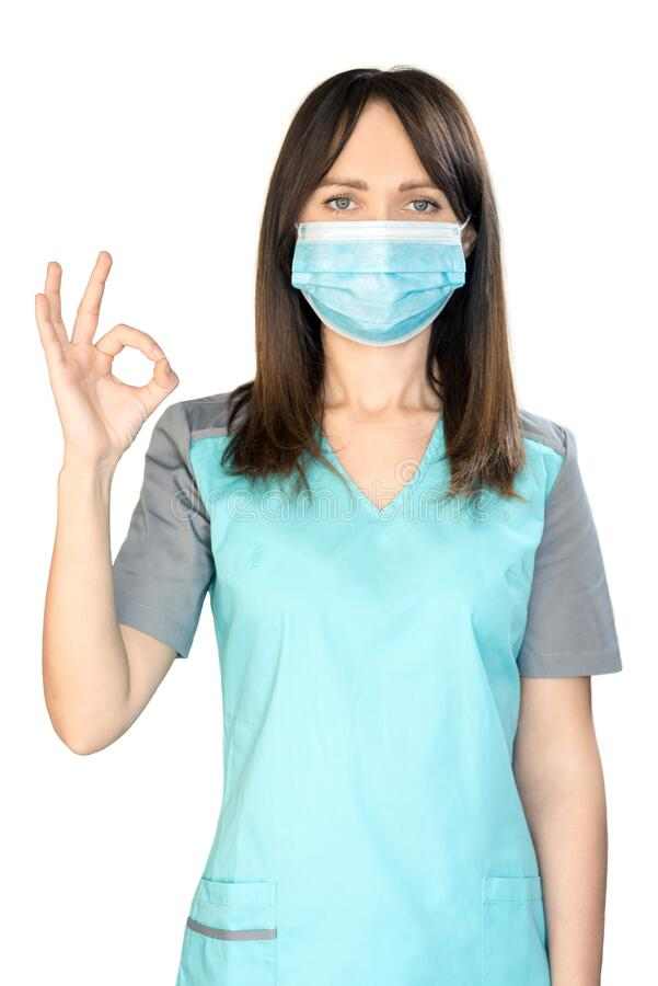 The topic of coronavirus and safety. Young female doctor with dark hair in a mask from a virus shows OK. vertical frame. The topic of coronavirus and safety stock images