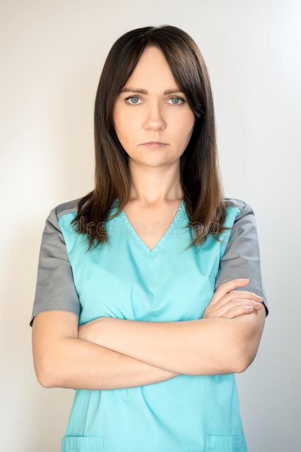 The topic of coronavirus and safety. Young serious female doctor in a surgical suit on a light background. Vertical frame. The topic of coronavirus and safety stock image