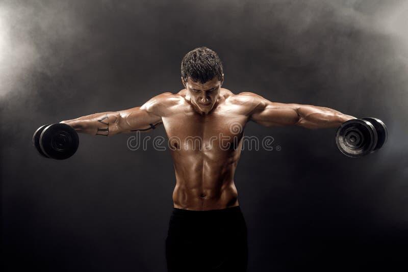 Toples mięśniowy mężczyzna robi ćwiczeniu z dumbbells zdjęcie royalty free