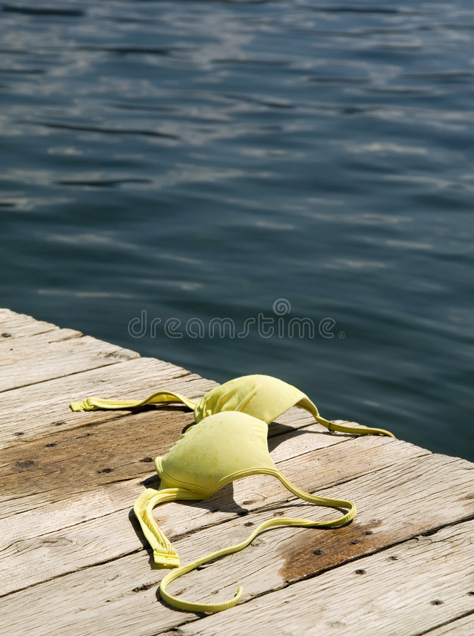 Topless at the beach. Bikini top left on pier stock images