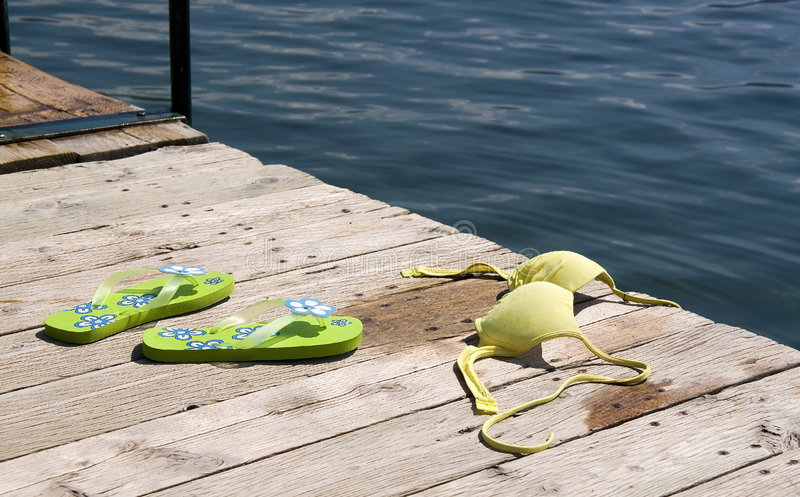 Topless at the beach. Bikini tp and flipflops on pier beside lake royalty free stock images