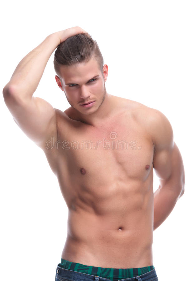 Topless fashion man with hand at the back. Young fashion topless man holding a hand at his back and holding his hair with the other. isolated on white background stock photo