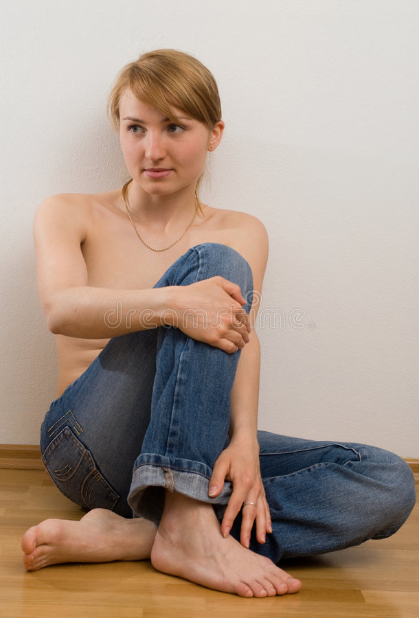Topless girl. A topless girl wearing jeans sitting on the floor stock photo