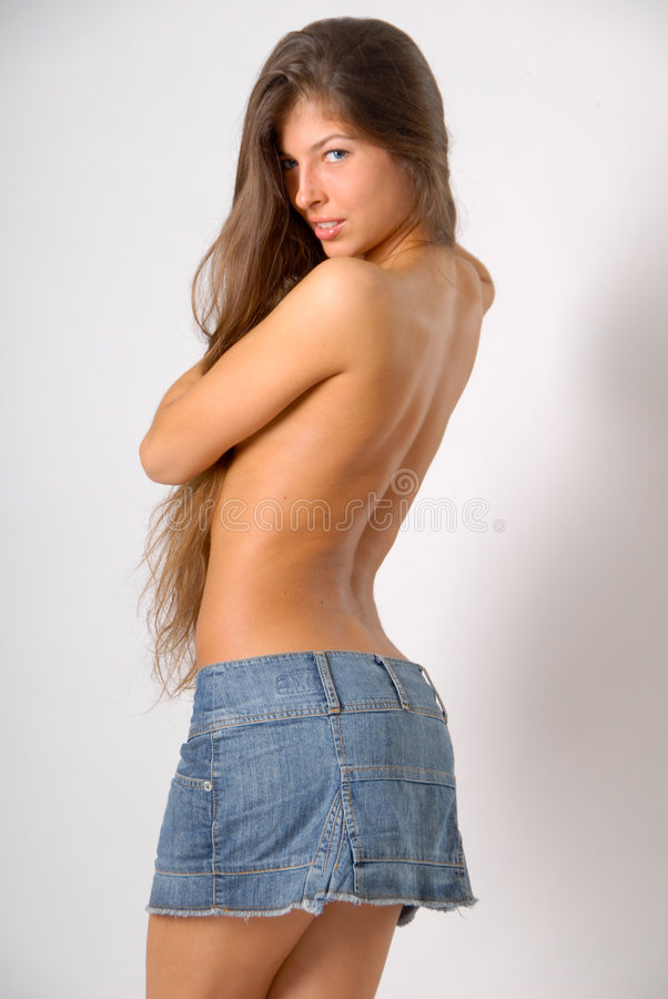 Topless girl. With long hair in skirt is covering her breasts with hair and holding shoes royalty free stock photos