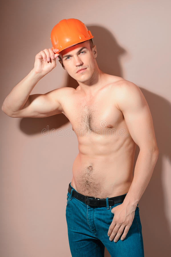Topless handsome man wearing hard hat stock photo