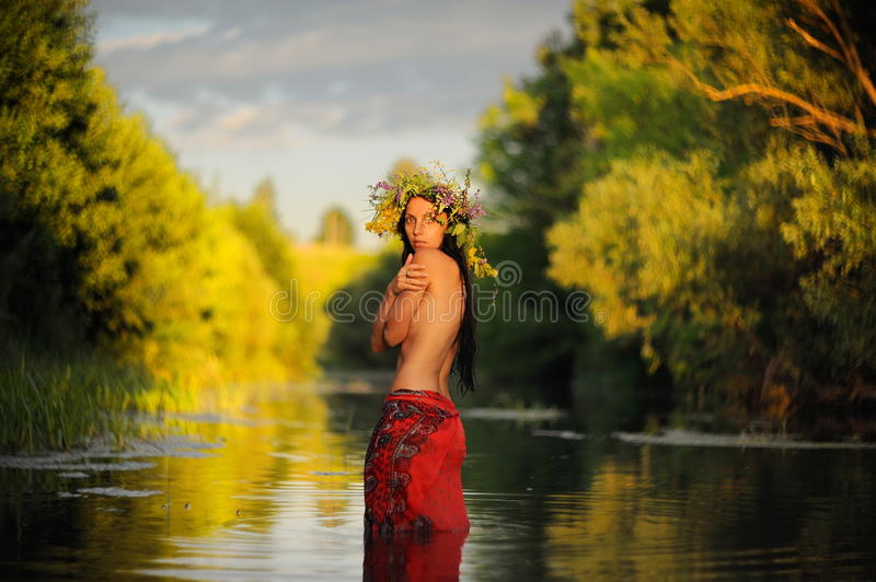 Topless long-haired brunette girl in red skirt and grass wreath. Standing in shallow river at sunset selective focus horizontal stock images