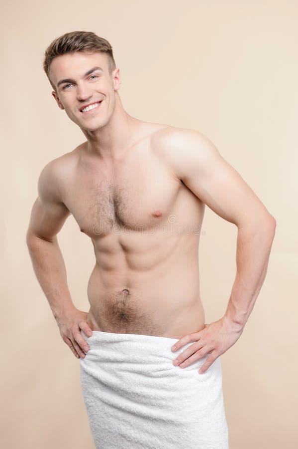Topless mens die zich met handdoek op heupen bevindt royalty-vrije stock afbeeldingen