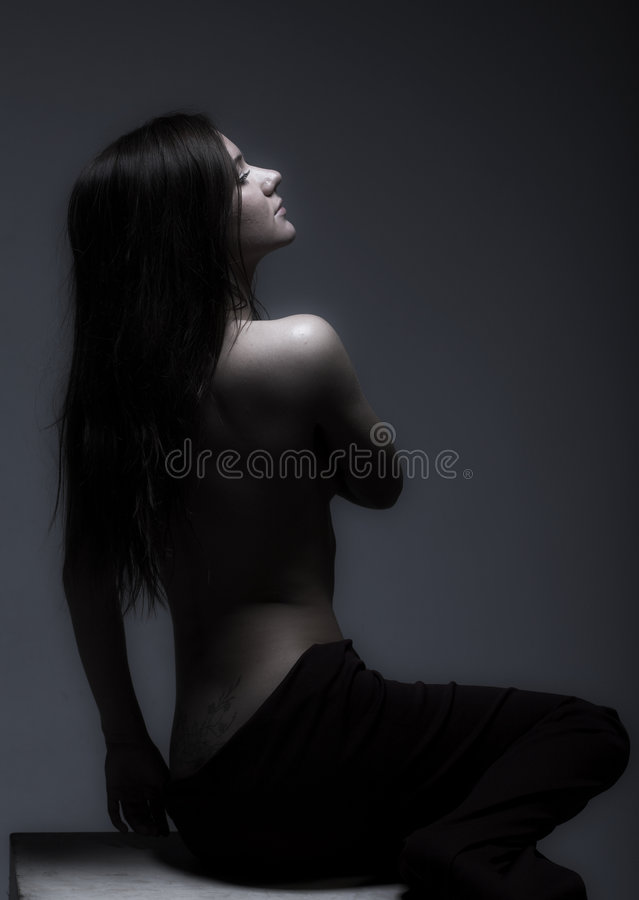 Topless modest girl. Studio portrait of a topless modest girl in semidarkness stock photography