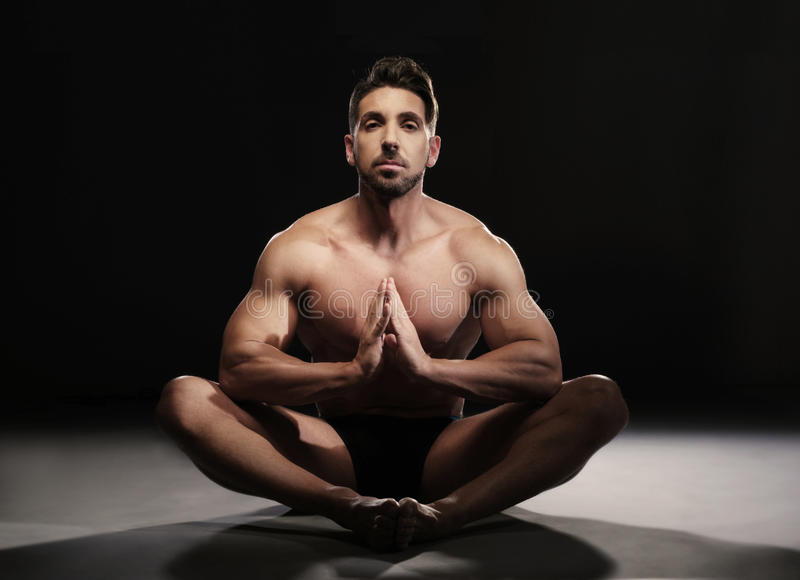 Topless Muscular Man Sitting in a Yoga Position. Portrait of a Topless Muscular Man Sitting on the Floor in a Yoga Position Looking at the Camera on a Black royalty free stock images