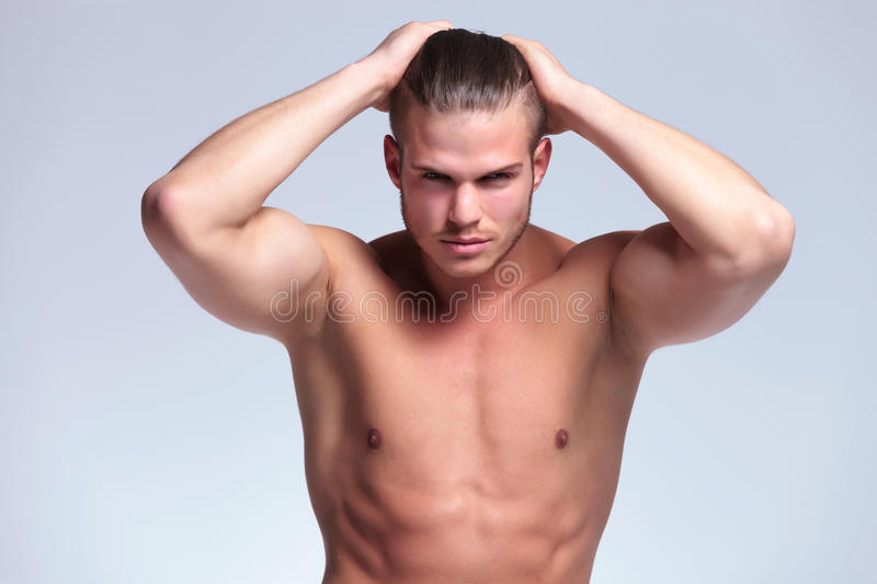 Topless young man with hands in hair. Young topless man adjusting his hair with both hands while looking at the camera. on gray background royalty free stock images