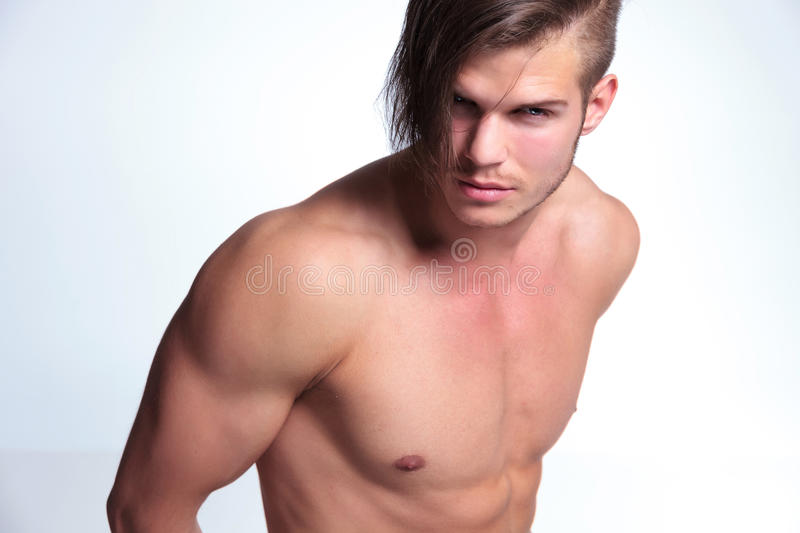 Topless young man with superb body. Young topless man with worked out body looking at the camera. on gray background stock photos