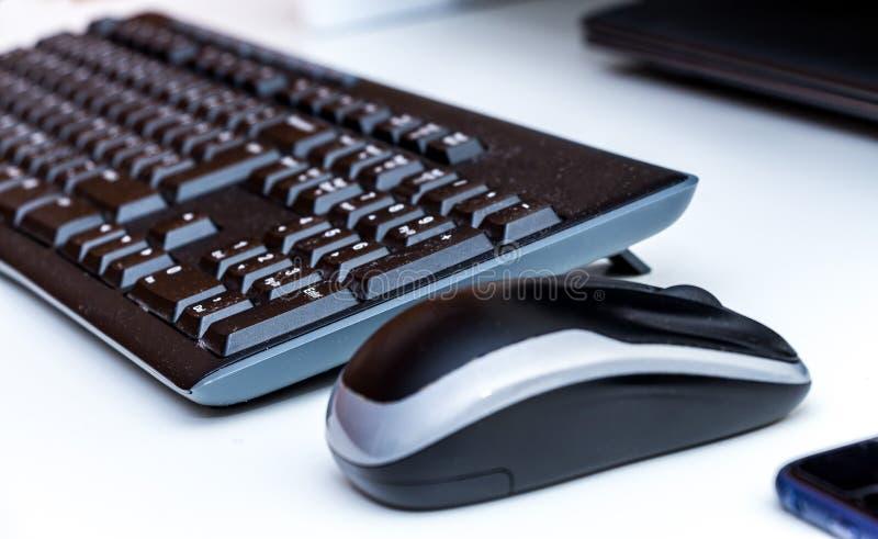Topo, tastiera e computer portatile senza fili del computer su uno scrittorio bianco fotografie stock libere da diritti