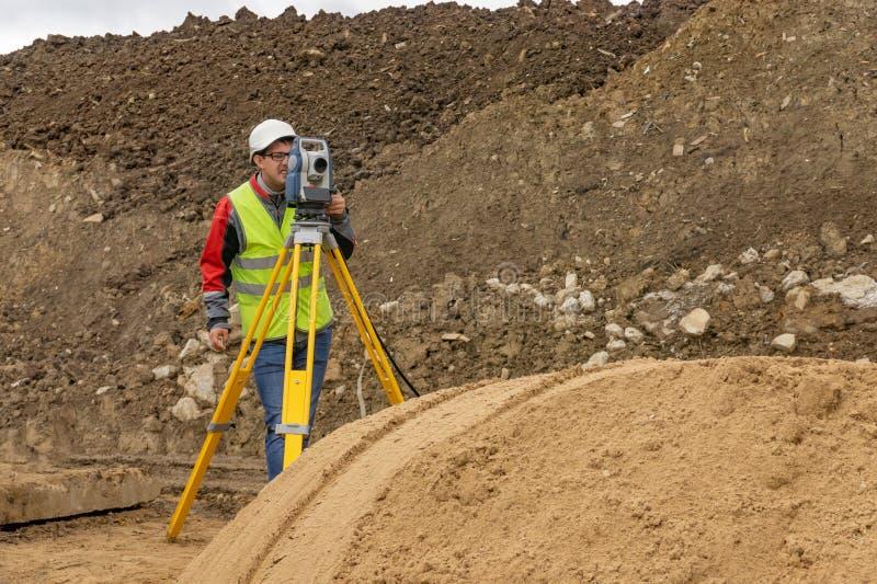 Topografisch onderzoek van het terrein door een landmeter stock fotografie