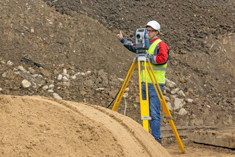Topografisch onderzoek van het terrein door een landmeter bij de bouwwerf royalty-vrije stock afbeelding