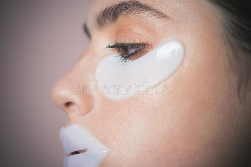 Toppe d'idratazione per gli occhi e le labbra Cattura della cura della sua pelle Toppe dell'occhio di prova della ragazza Routine fotografia stock libera da diritti