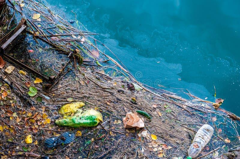 Toppe dell'immondizia e dell'olio di inquinamento delle acque le vecchie sull'acqua sorgono fotografie stock libere da diritti