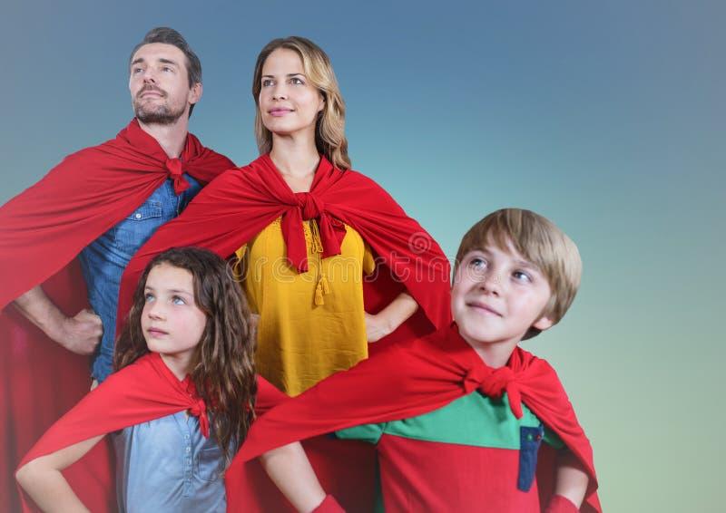 Toppen familj som bär rött uddeanseende med handen på höft mot klar himmelbakgrund arkivbild