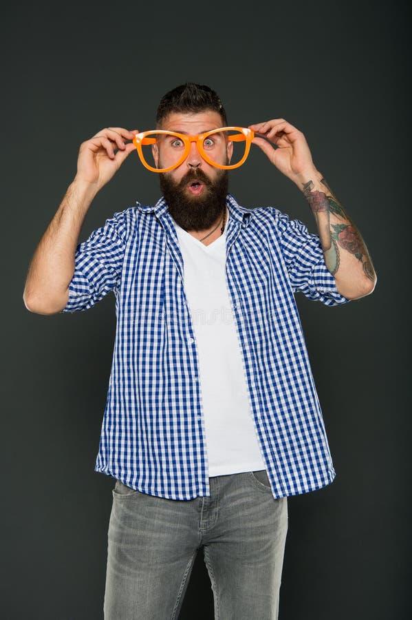 Toppen galen överraskning Galen hipster på grå bakgrund Förvånad skäggig man som bär roliga exponeringsglas med galen blick arkivfoto