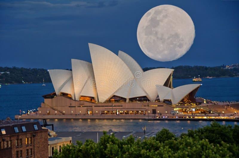 Toppen måne över Sydney Opera House arkivbild