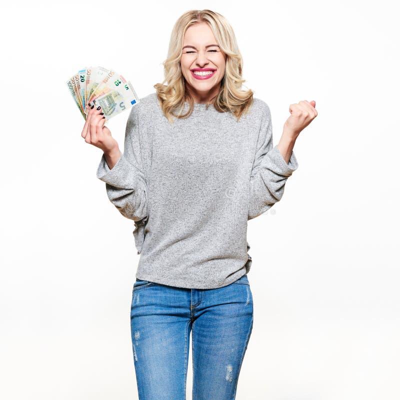 Toppen upphetsad ung kvinna i grå tröja och jeans som rymmer gruppen av eurosedlar, fästande nävar som firar royaltyfri fotografi