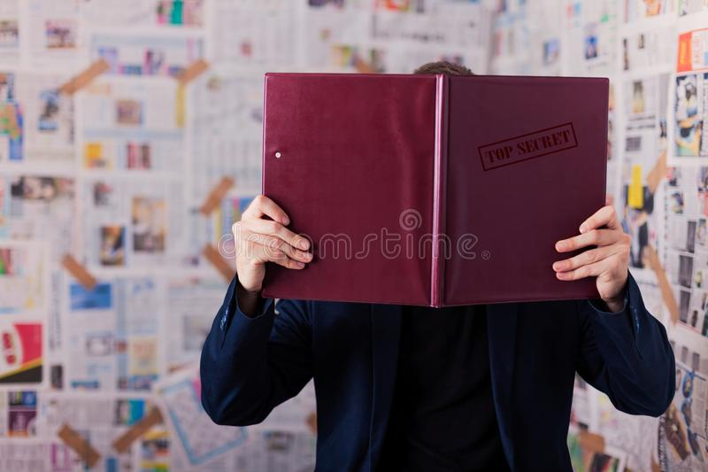Topphemlig mapp Få information Läs- mapp, mapp på stolen arkivfoto