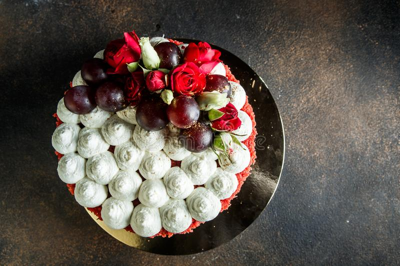 Topping of cake decorated with bizet, grapes and roses. Topping of beautiful cake decorated with white bizet, grapes and roses royalty free stock photos