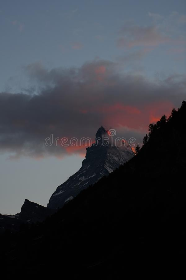 Toppmöte av det matterhorn berget som täckas av rödfärgade moln arkivfoton