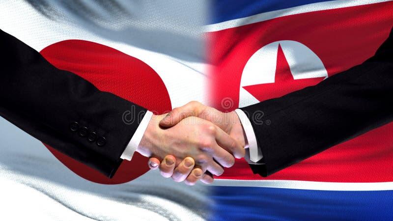 Toppmöte för kamratskap för Japan och Nordkorea handskakning internationell, flaggabakgrund fotografering för bildbyråer